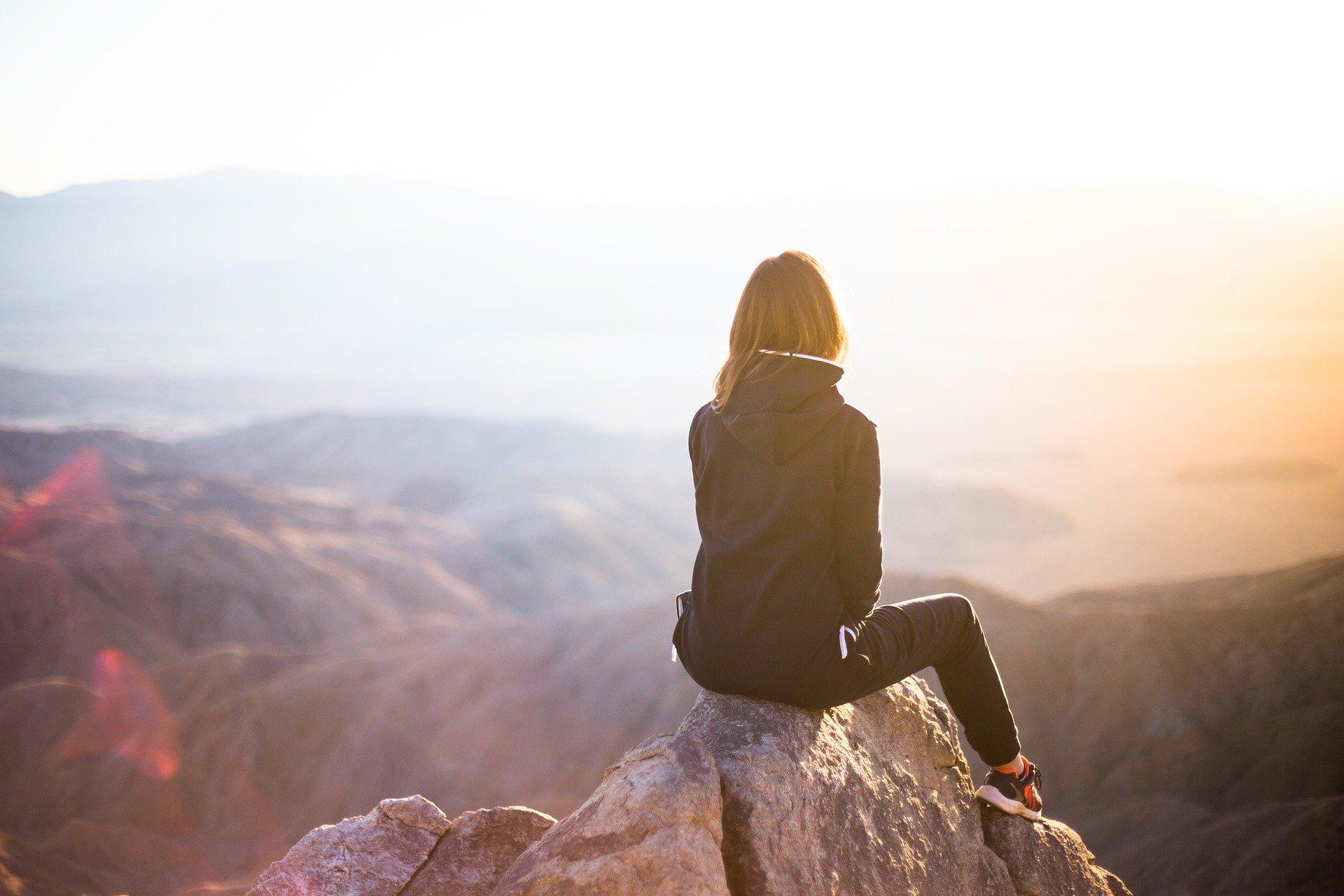 Frau auf Berg bei Sonnenuntergang